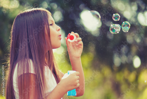 Poster Artist KB Young female child blowing soap bubbles