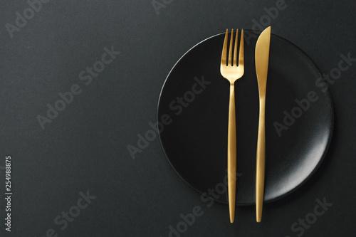 Fototapeta Gold cutlery set on black background obraz