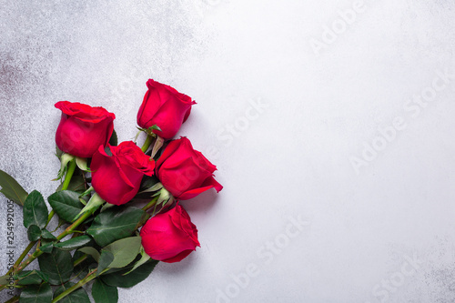 Red rose flowers bouquet on stone background Greeting card Copy space