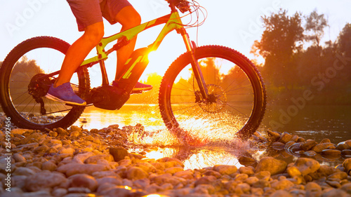 Fototapety, obrazy: TIME REMAP: Cool shot of mountain biker riding across a river on golden morning.