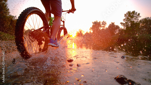 Carta da parati LENS FLARE: Sportsman riding his bicycle in the shallow stream towards sunset