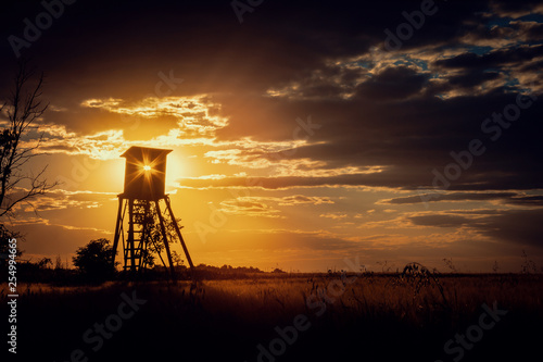 Poster Chasse Dark Sunset Landscape with Sun in Hunting Tower