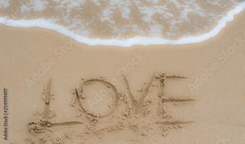 Photo la palabra amor escrita en la arena de la playa