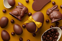 Easter Composition With Chocolate Eggs And Bunnies On Yellow Background, Holiday Concept