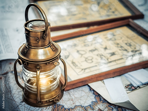 Photo Stands Ship Old brassy ship lantern stands on a map of the seas near pictures with the image of sea knots