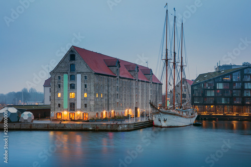 Canvas Prints Ship giant old sailboat in water and old warehouse building in morning twilight in Copenhagen in Denmark