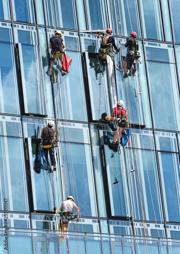 Fotografía  Group of construction workers working at height on modern commercial skyscraper,