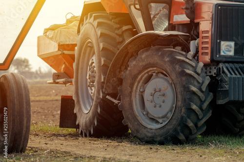 Stary czerwony ciągnik rolniczy z przyczepą na drodze brud wsi