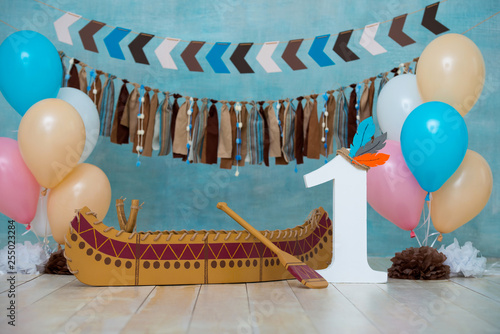 Photo Decorated photo zone for 1 year Indian Apache chief with a canoe for a children's party