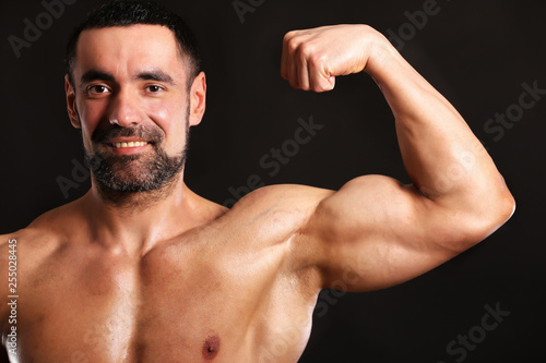 Fotografie, Obraz  Porter of young muscular man on black background show him body , bodybuilding ,s