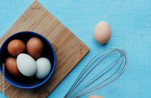 Brown and blue chicken eggs on wooden board with whisk for cooking food.