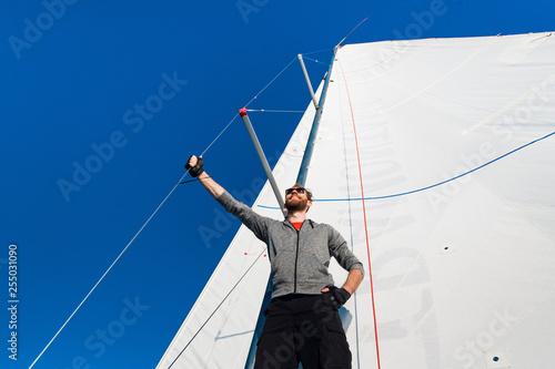 Cuadros en Lienzo Yacht captain with a beard stands on sail boom on a sailing yacht, holding the rope in his hand and smiling, feeling happy