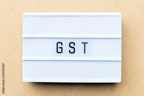 Fotografía  White lightbox with word GST (Abbreviation of Goods and Service Tax) on wood bac