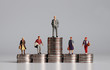 canvas print picture - Miniature people with stack of coins. A concept of income inequality.
