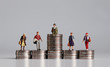 canvas print picture - Social stratification concept. Miniature people with stack of coins.