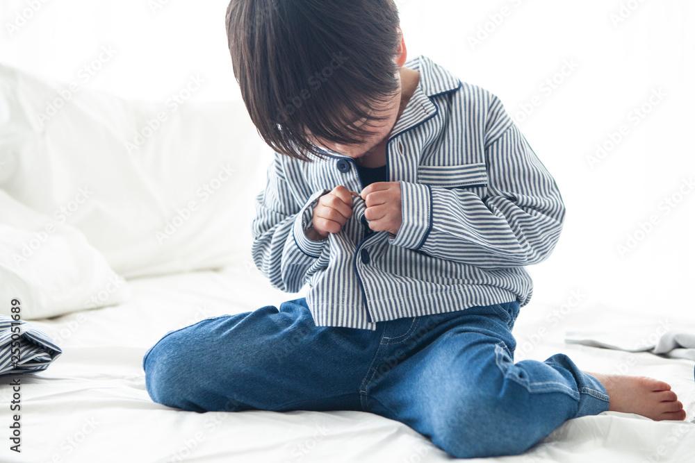 Fototapety, obrazy: パジャマのボタンを閉めようとする男の子