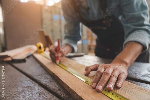 Fotografia Carpenter working with equipment on wooden table in carpentry shop