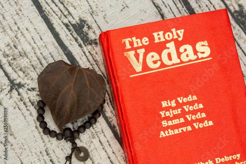 Vászonkép Maski,Karnataka,India - March 13,2019 :The Holy Vedas on wooden textured backgro