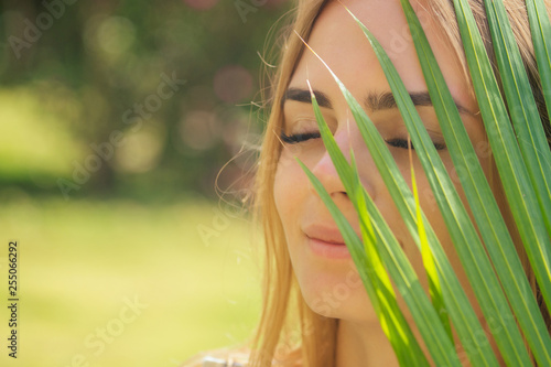 close up portrait face blond woman thick eyebrows like Cara Delevingne with palm фототапет