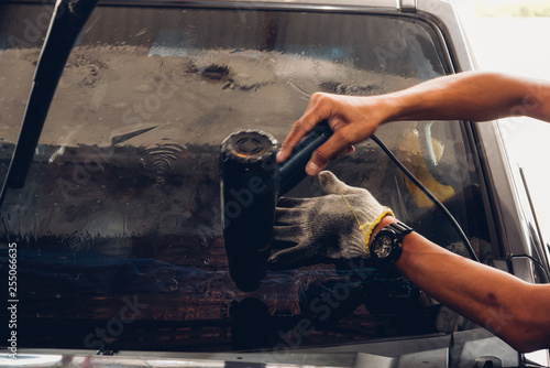 Man specialist attached window film by hot gun on car Canvas Print