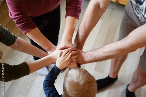 Fotografía  Stack of family people hands - father with children on light brown wooden texture laminate floor background indoors, little boy in middle