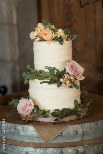 Fotomural wedding cake with real roses and greenery on a wine barrel