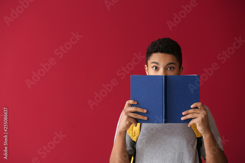 Photo  African-American schoolboy with book on color background