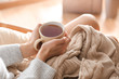 Leinwandbild Motiv Young woman drinking hot tea at home, closeup