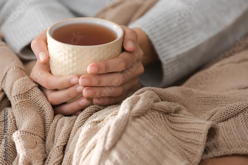 Canvastavla Young woman drinking hot tea at home, closeup