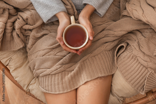 Young woman drinking hot tea at home Wallpaper Mural