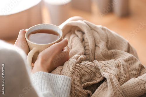 Poster Thee Young woman drinking hot tea at home, closeup