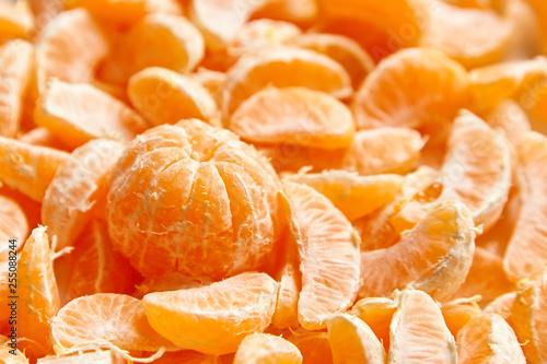 Fotografía  Peeled tangerine. Segments of mandarin fruit background