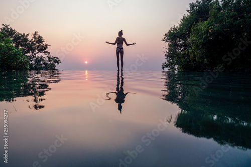 Beautiful woman practice yoga pose on the pool above the Mountain peak in the evening in front of beautiful nature views in india goa wildernest nature resorte .romance sunset in the mountains