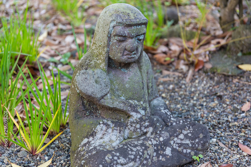 Fotografía  Old statue of a seated Buddhist monk made of stone close-up