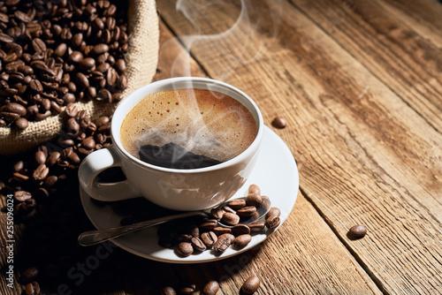 Czarna kawa na starych deskach i rozsypane ziarna - 255096024