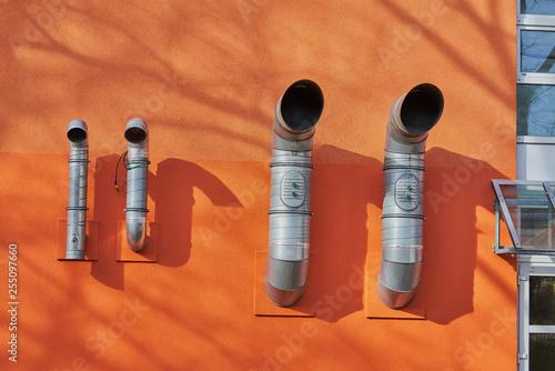 Valokuva  Lüftungsrohre an einer orangen Hauswand