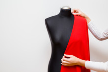 Woman's Hands Measuring Red Fabric On Black Mannequin For Dress Sewing. Right Size. Handmade Work. Feminine Hobby. Gray Background. Front View.