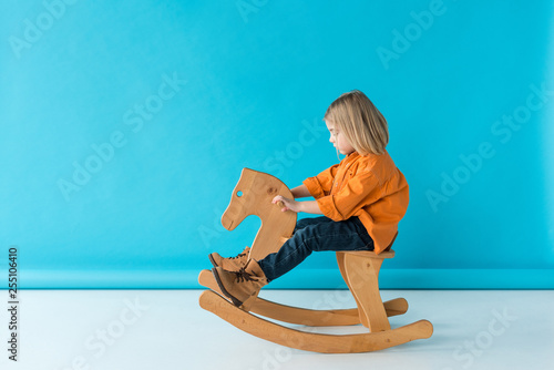 side view of blonde and cute kid riding on rocking horse on blue background Tapéta, Fotótapéta