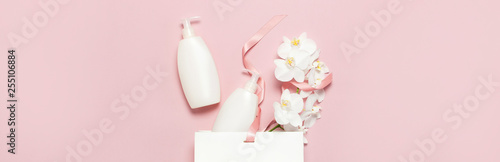 Poster Spa Flat lay top view White cosmetic bottle containers gift bag White Phalaenopsis orchid flowers on pink background. Cosmetics SPA branding mock-up Natural organic beauty product concept Minimalism style