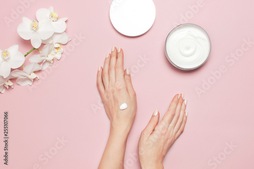 Poster Spa Young woman moisturizes her hand with cosmetic cream lotion opened container with cream body milk White Phalaenopsis orchid flowers on pink background Flat lay top view minimalism style Beauty concept