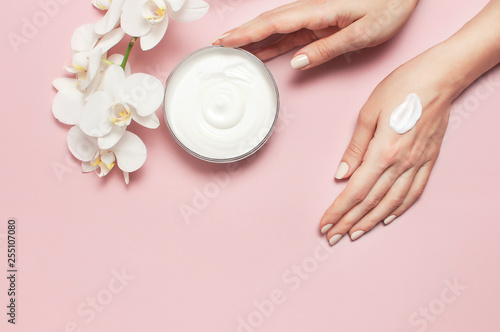 Fotografía Young woman moisturizes her hand with cosmetic cream lotion opened container wit