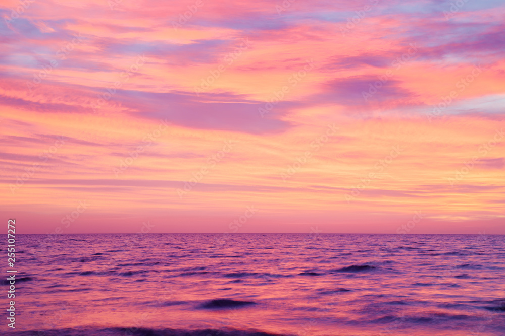 Fototapety, obrazy: Small, blurry waves of sea and burning purple pink sunset sky. Peaceful atmosphere at beach. Nice nature background.