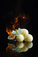 Exotic Passion Fruit Ice Cream With Flower And The Fire On The Black Glass Background