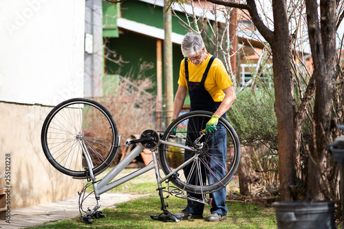 Fotografía  Man lubricating bicycle chain maintaining for the new season