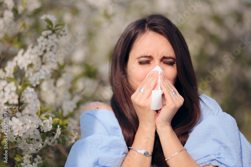 Fényképezés  Allergic Woman Blowing Her Nose Next to Blooming Tree