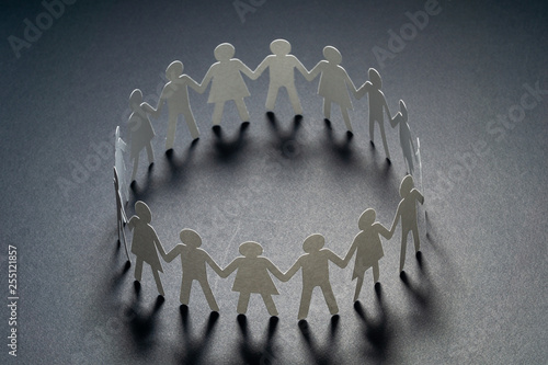 Fotografie, Obraz Circle of paper people holding hands on dark surface