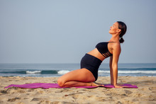 Young Pregnant Woman Doing Yoga Exercises On The Beach