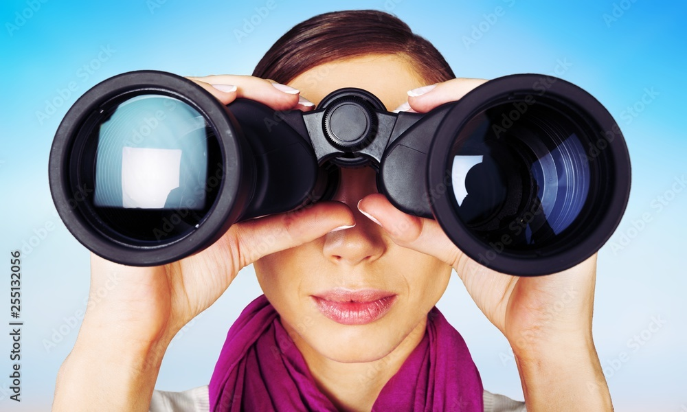 Fototapeta Girl looking into binoculars on light background