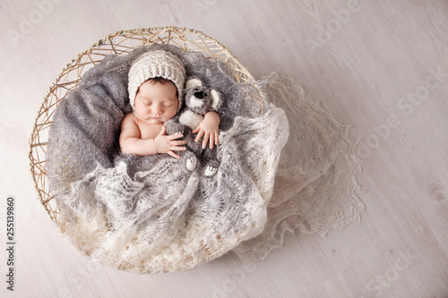 Photo Sweet newborn baby sleeps in a basket