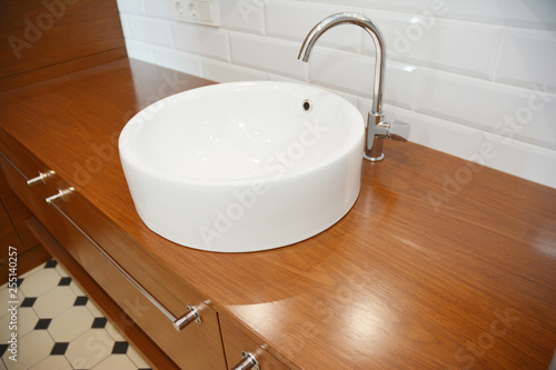 Fotografia, Obraz  Bathroom ceramic sink with chome water tap and wooden table.